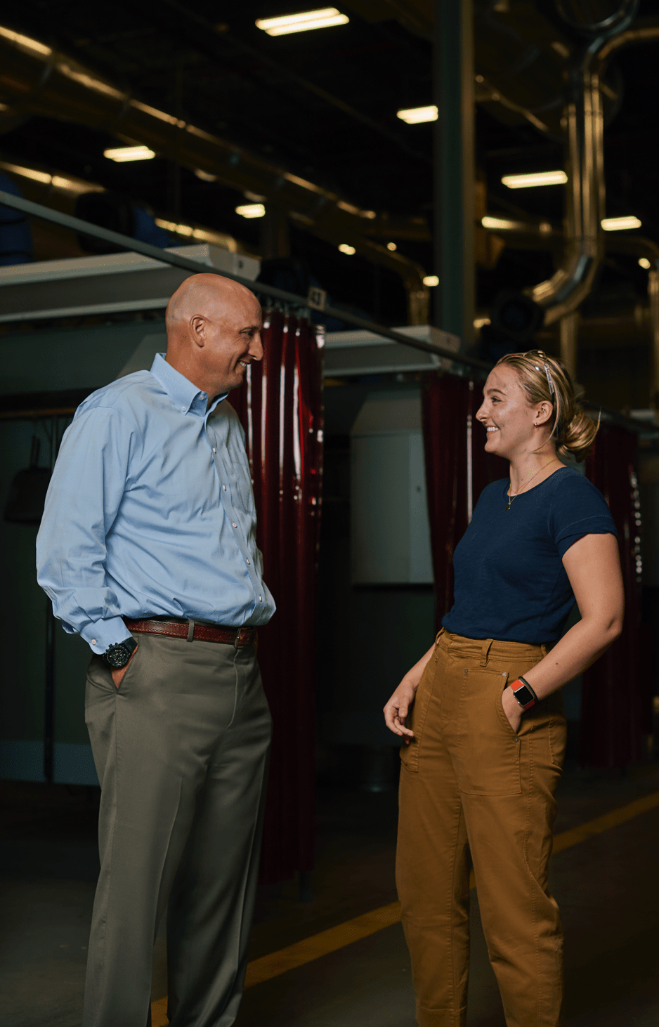 A Male Attorney and a Woman Talking in a Factory