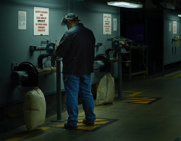 A Worker at a Grinding Machine